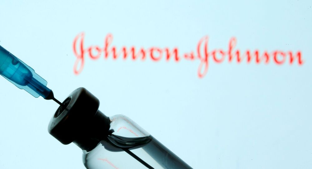 A vial and sryinge are seen in front of a displayed Johnson&Johnson logo in this illustration taken January 11, 2021