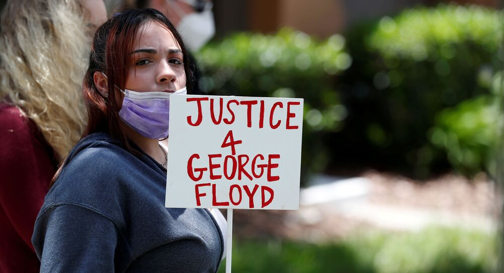 A protester holds a sign outside the Florida home of former Minneapolis police officer Derek Chauvin, who was recorded with his knee on the neck of African-American man George Floyd