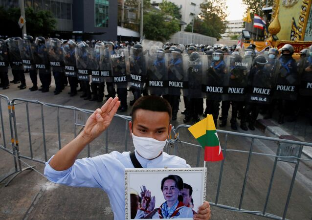 A Myanmar citizen holds Aung San Suu Kyi portrait as he joins with Thai protesters an anti-government protest in Bangkok, Thailand February 28, 2021.