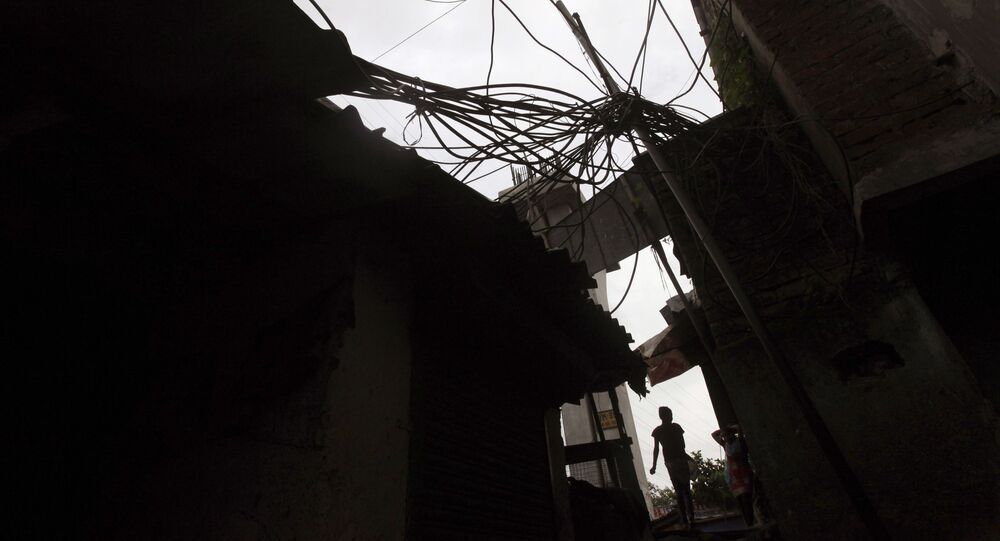 An Indian girl walks a narrow lane beneath a power pole with high-voltage cables coiling around at a slum in Mumbai, India, Friday, Aug. 3, 2012