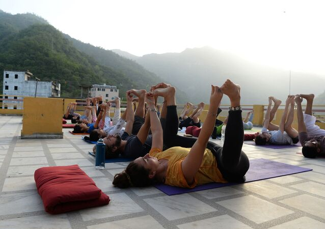 This picture taken on June 19, 2018, shows people practising yoga on a terrace at the Anand Prakash yoga ashram in Rishikesh in India's Uttarakhand state