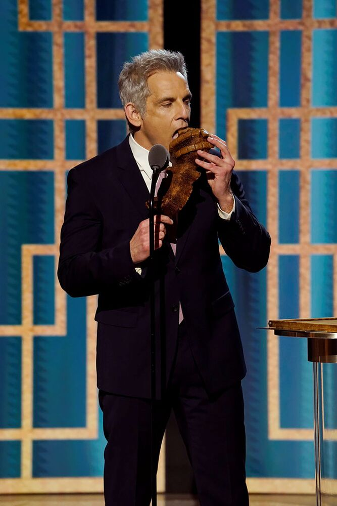 Ben Stiller jokes as he eats bread shaped like a Golden Globe trophy in this handout photo from the 78th Annual Golden Globe Awards in New York, 28 February 2021.