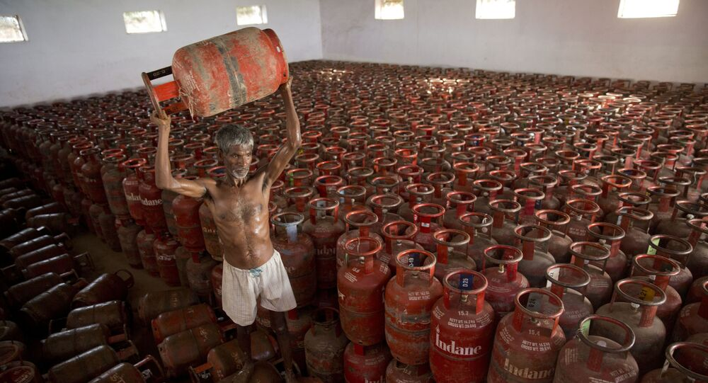 An Indian laborer sorts Liquid Petroleum Gas (LPG) cylinders used for cooking at a warehouse after downloading them from  a truck in Allahabad, India, Monday, Aug.1, 2016
