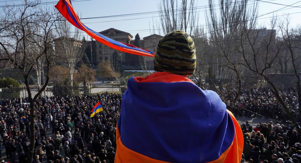 An opposition supporter wrapped in a national flag attends a rally to demand the resignation of Armenian Prime Minister Nikol Pashinyan, in Yerevan, Armenia February 27, 2021