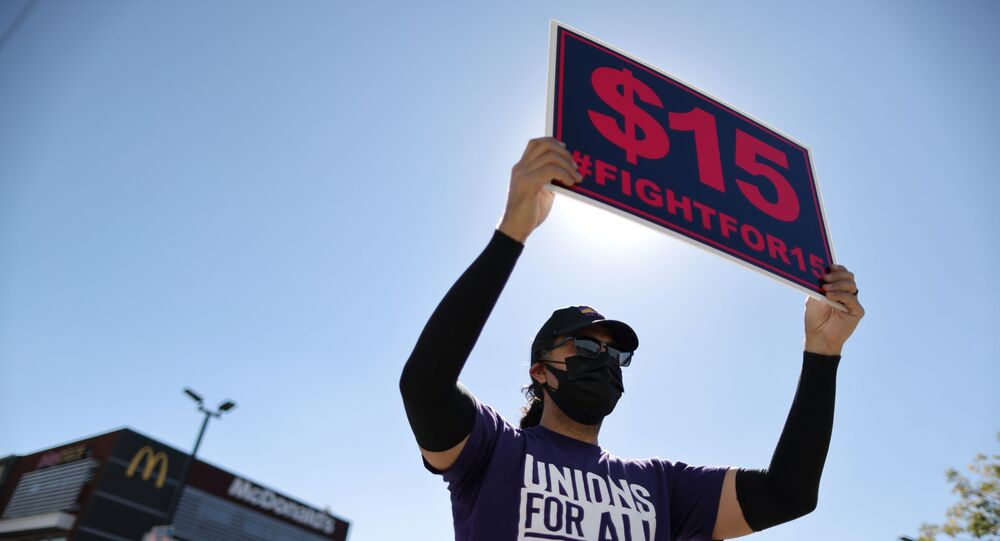 A man holds up a minimum wage sign at a rally held by fast food workers and supporters to celebrate the California Labor Commissioner's order for the company to rehire and compensate workers who went on strike for coronavirus disease (COVID-19) protections, in Los Angeles, California, U.S., February 18, 2021. REUTERS/Lucy Nicholson