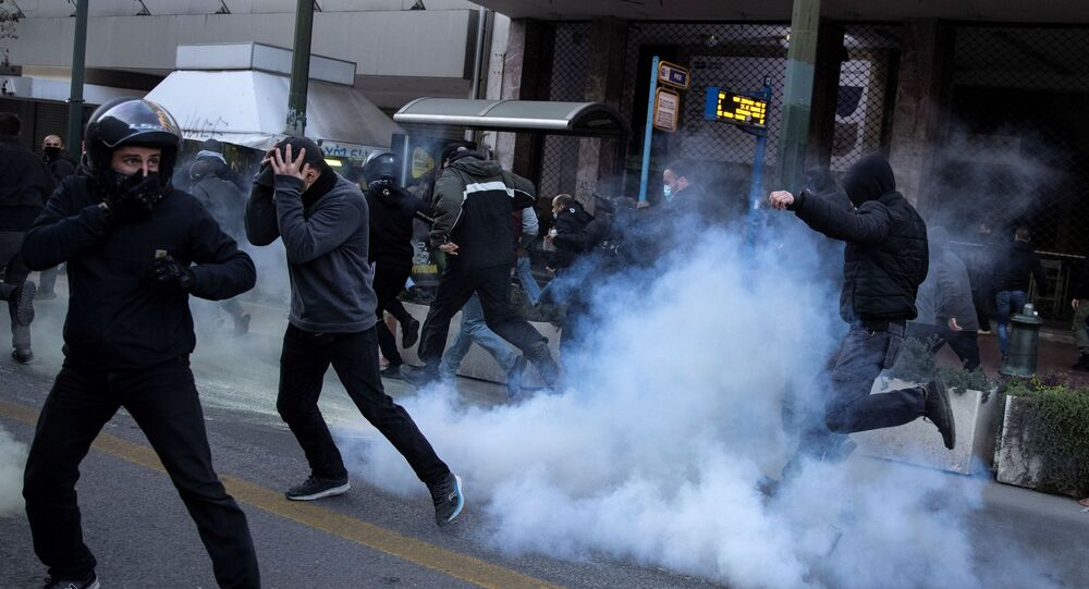 Protesters flee from tear gas as they clash with riot police during a demonstration in support of hunger striker Dimitris Koufodinas.