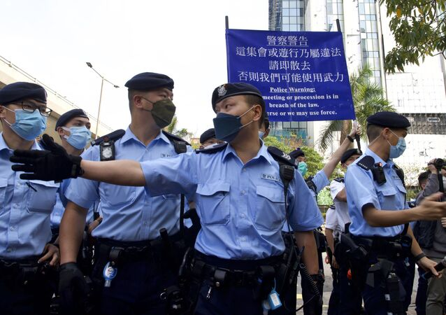 Police officers raise a warning flag against supporters gathered outside a court in Hong Kong Monday, March 1, 2021. Hong Kong police on Monday brought 47 pro-democracy activists to court on charges of conspiracy to commit subversion under the national security law imposed on the city by Beijing last year.