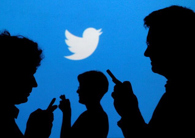 People holding mobile phones are silhouetted against a backdrop projected with the Twitter logo in this illustration picture taken September 27, 2013