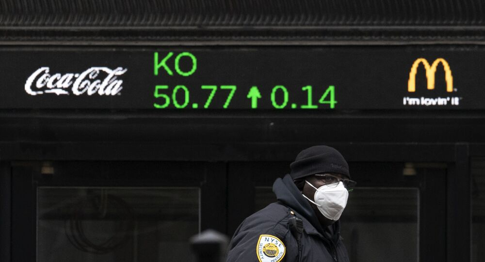 A security guard walks by a stock ticker displaying the cost of Coca-Cola shares at the New York Stock Exchange, Tuesday, Feb. 23, 2021.