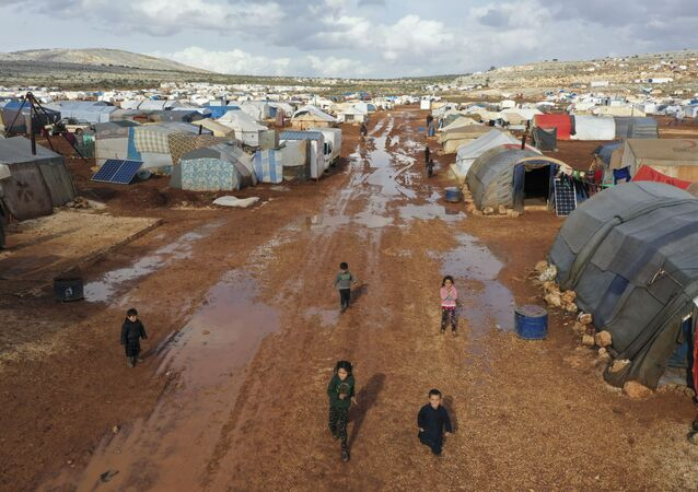 Syrian refugees walk through a camp for displaced muddied by recent rains near the village of Kafr Aruq , in Idlib province, Syria, Thursday, Jan. 28, 2021.