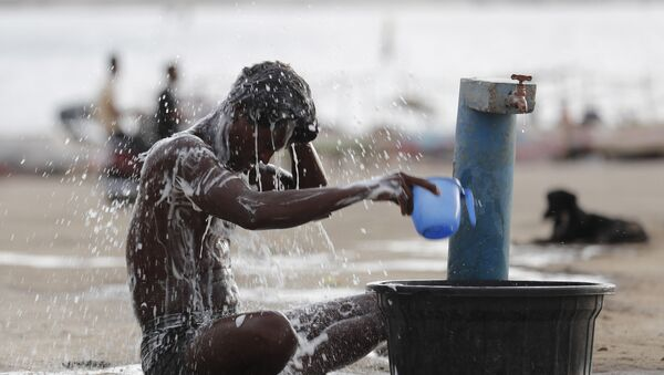 A man bathes at a public water tap near the River Ganges during a hot summer day in Prayagraj, India, Wednesday, May 27, 2020 - Sputnik International
