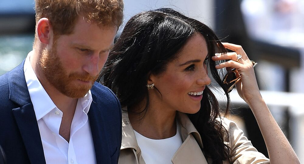 (FILES) In this file photo Britain's Prince Harry and wife Meghan arrive for a public walk at the Sydney Opera House in Sydney on October 16, 2018