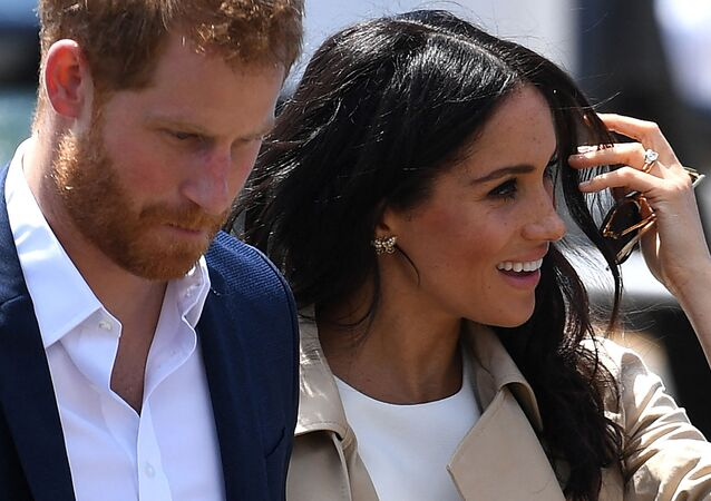 (FILES) In this file photo Britain's Prince Harry and wife Meghan arrive for a public walk at the Sydney Opera House in Sydney on 16 October 2018