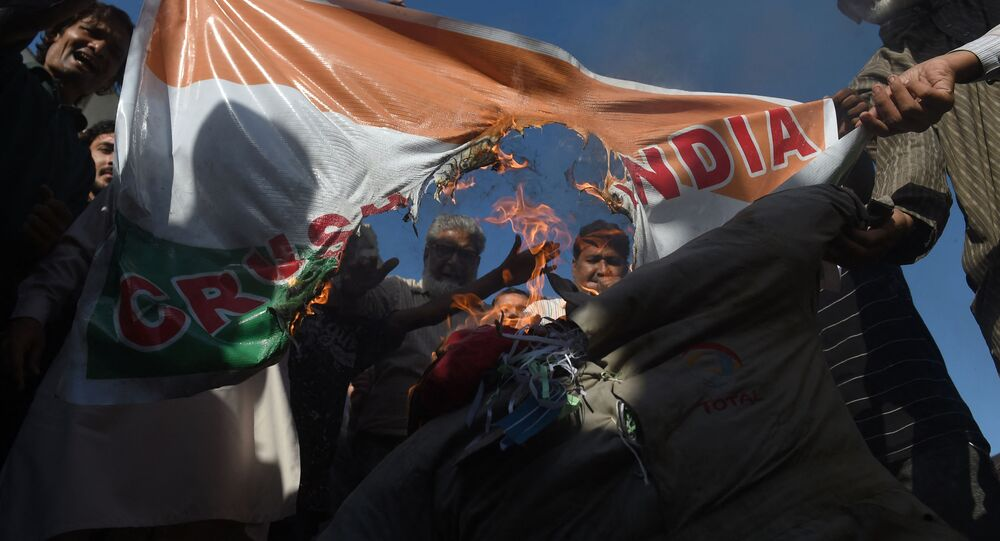 Protesters burn an effigy of Indian Prime Minister Narendra Modi and an Indian flag during a rally against the recent sectarian violence in India's capital over the controversial citizenship law, in Karachi on March 4, 2020