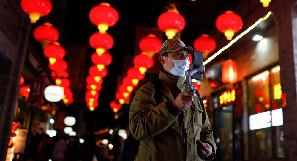 A man wearing a face mask following an outbreak of the coronavirus disease (COVID-19) uses his phone while walking near the Qianmen street ahead of Lunar New Year celebrations, in Beijing, China February 10, 2021