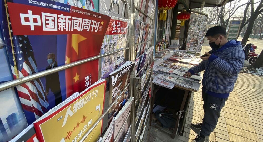 A newsstand vendor looks through his display near a magazine with a cover depicting U.S. President Joe Biden near U.S. and Chinese flags in Beijing on Thursday, Jan. 21, 2021