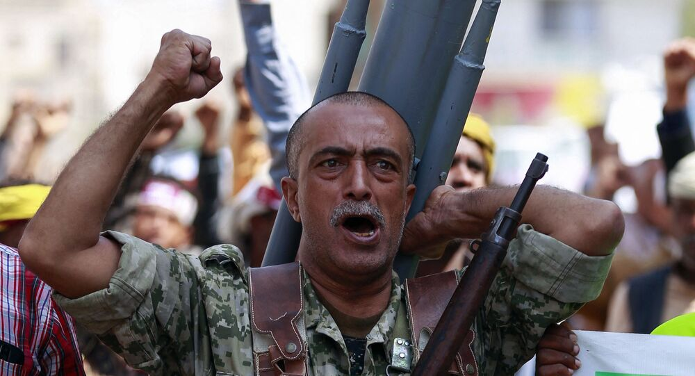 A fighter loyal to Yemen's Huthi rebels carrying a mock missile bearing anti-US slogans on his back chants during a rally commemorating the death of Shiite Imam Zaid bin Ali in the capital Sanaa, on September 14, 2020.