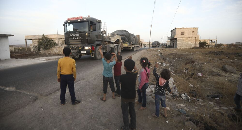 Turkish military convoy drives through the village of Urum al-Jawz, in Idlib province, Syria, Tuesday, Oct. 20, 2020.