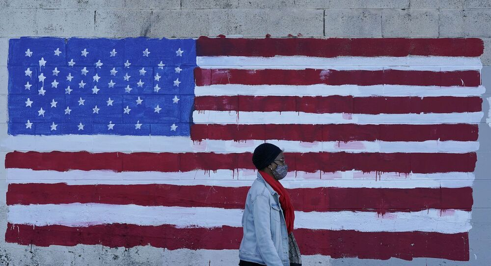 In this Nov. 16, 2020, file photo, a woman wears a mask while walking past an American flag painted on a wall during the coronavirus outbreak in San Francisco.