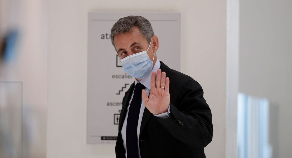 Former French President Nicolas Sarkozy waves during a break in his trial on charges of corruption and influence peddling, at Paris courthouse, France, November 30, 2020.