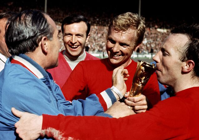Bobby Moore (centre) and Nobby Stiles (right) shares the trophy with manager Alf Ramsey after England win the World Cup in 1966