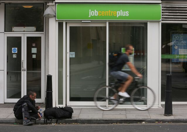 A cyclist passes the entrance to a job centre in east London on July 20, 2016