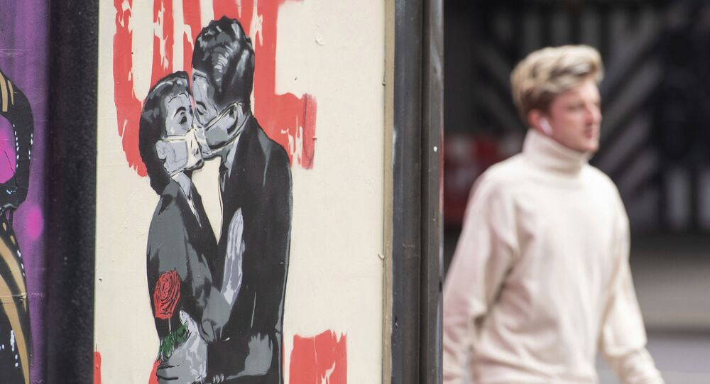 A man passes a poster showing a couple wearing protective face masks embracing in Shoreditch area of east London, following the introduction of measures to bring England out of the coronavirus lockdown, Thursday June 4, 2020