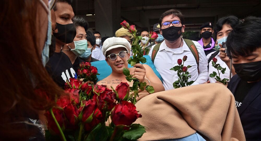 Anti-government blues musician Ammy The Bottom Blues receives flowers as he is wheeled on a hospital bed outside the Office of the Attorney General in Bangkok on February 17, 2021, before the state prosecutor decided whether to indict 18 activists on charges including sedition and lese majeste related to anti-government protests in 2020.