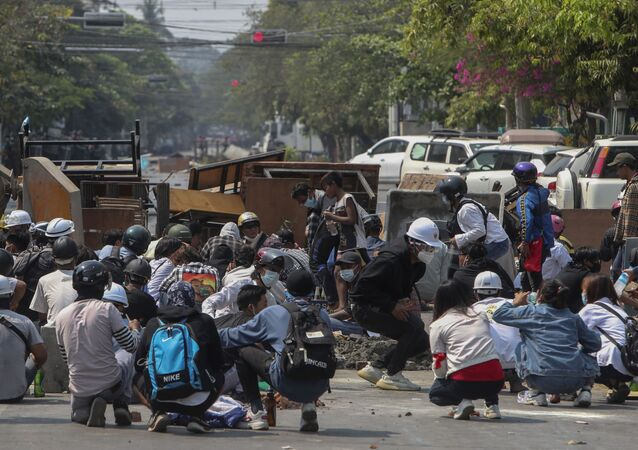 Anti-coup protesters take cover behind makeshift barricades in Mandalay, Myanmar, Wednesday, March 3, 2021. Demonstrators in Myanmar took to the streets again on Wednesday to protest last month's seizure of power by the military