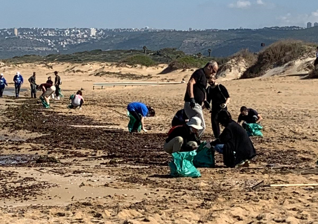 Clean up operation along Israel's Mediterranean coastline by employees of Elbit Systems, a major Israeli defence electronics company.
