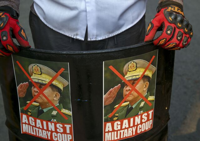 An anti-coup protester displays defaced images of Commander in chief, Senior Gen. Min Aung Hlaing in Mandalay, Myanmar, Wednesday, March 3, 2021.