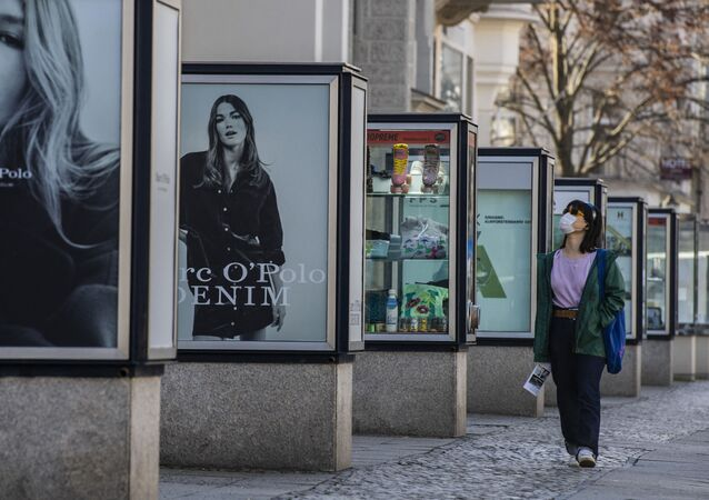 A woman wearing a face mask walks by advertising booths on Berlin's Kurfuerstendamm shopping mile on March 3, 2021, during the ongoing coronavirus (Covid-19) pandemic.
