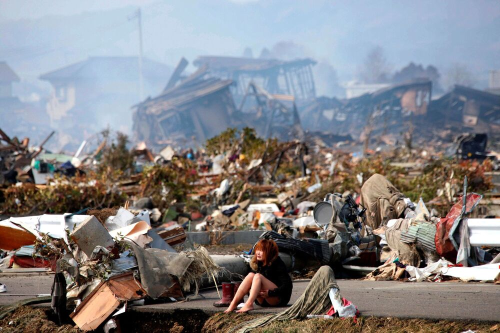 A woman sits on a road and cries in the destroyed city of Natori, Miyagi Prefecture in northern Japan 13 March 2011, after a massive earthquake and tsunami.