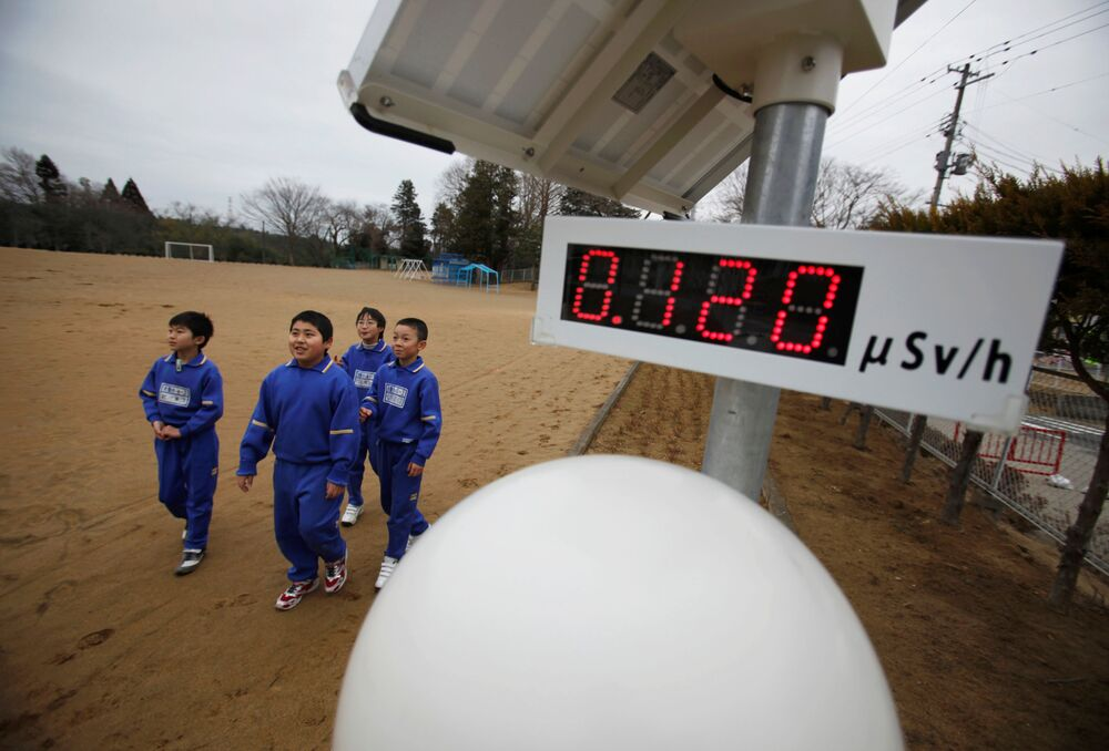 Students walk near a Geiger counter, measuring a radiation level of 0.12 microsieverts per hour, at Omika Elementary School, about 21 km from the crippled Fukushima Daiichi nuclear power plant, in Minamisoma, Fukushima prefecture, 8 March 2012, just three days before the first anniversary of the tsunami.