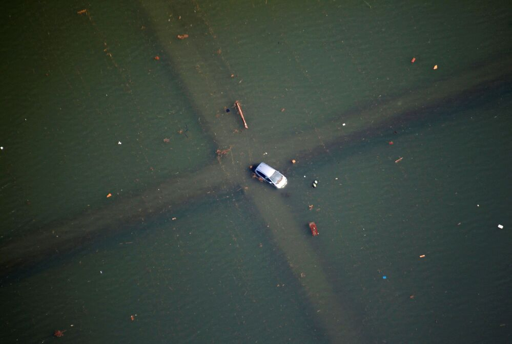 A half-submerged vehicle is seen at a crossroad after an earthquake and tsunami in Sendai, northeastern Japan, 12 March 2011.
