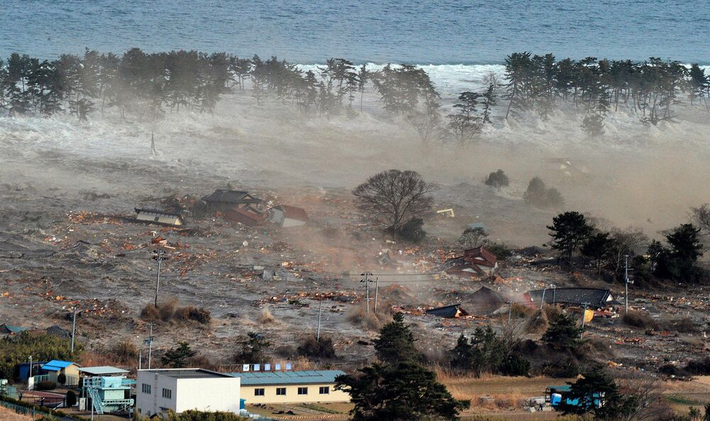 Houses are swept by a tsunami in Natori City in northeastern Japan 11 March  2011, in this photo taken by Kyodo.