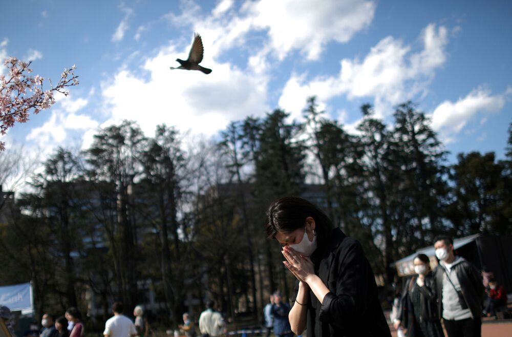 A woman wearing a protective face mask to guard against the coronavirus, prays during a memorial service at Hibiya Park in Tokyo, Japan, on 11 March 2020, to mark the ninth anniversary of the earthquake and tsunami that killed thousands and started a nuclear crisis.