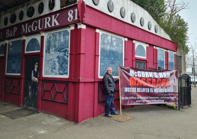 Campaigners stand outside the derelict McGurk's Bar in Belfast