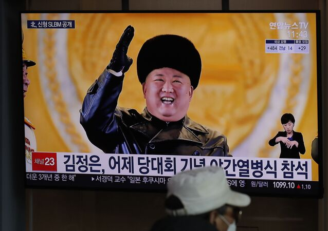 A man wearing a face mask sits in front of a TV screen showing North Korean leader Kim Jong-un, at Seoul Railway Station in the South Korean capital on Friday 15 January 2021.