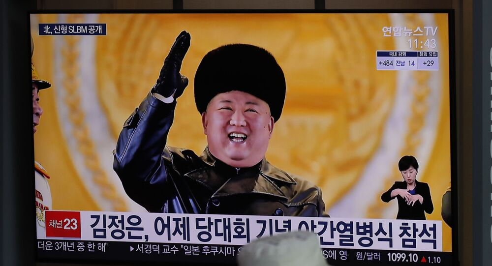 A man wearing a face mask sits in front of a TV screen showing North Korean leader Kim Jong Un, at the Seoul Railway Station in Seoul, South Korea, Friday, Jan. 15, 2021