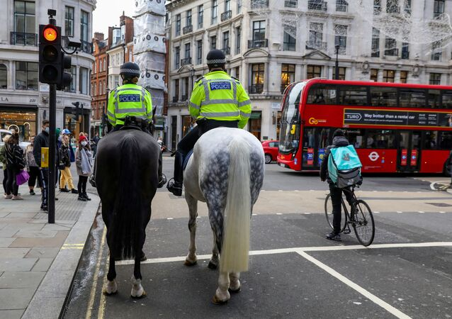 FILE PHOTO: Mounted police and a Deliveroo rider wait at a red light at Regent Street, one of London's main shopping streets, a day after a new lockdown was announced during the coronavirus disease (COVID-19) outbreak in London, Britain November 1, 2020