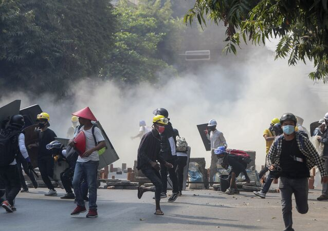 Anti-coup protesters run from teargas and charging riot police and soldiers in Mandalay, Myanmar, Wednesday, March 3, 2021