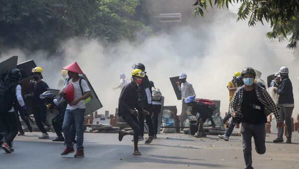 Anti-coup protesters run from teargas and charging riot police and soldiers in Mandalay, Myanmar, Wednesday, March 3, 2021 - Sputnik International
