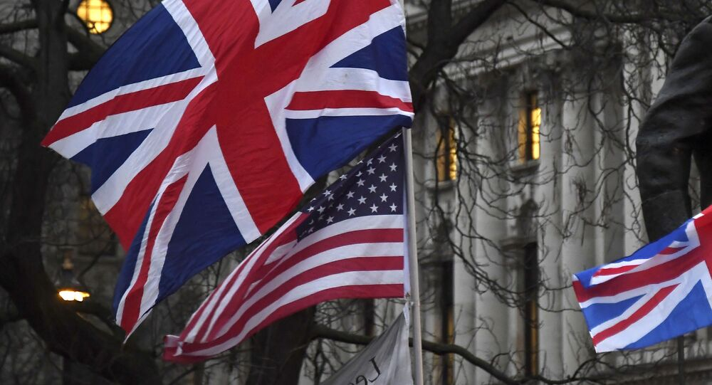 In this file photo dated Friday, Jan. 31, 2020, Brexit supporters hold British and US flags during a rally in London.