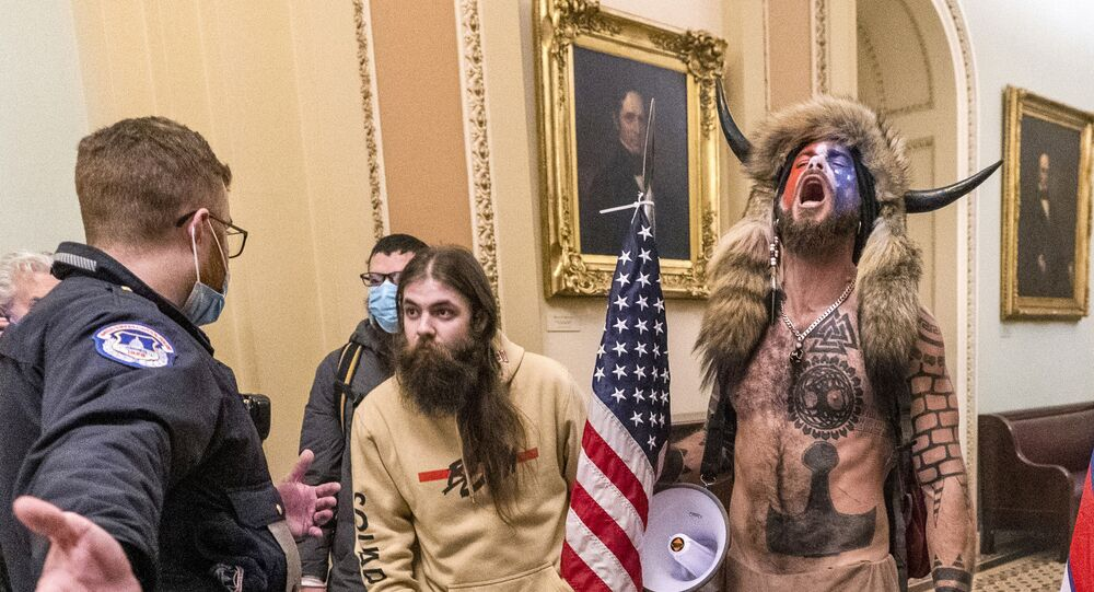 FILE - In this Wednesday, Jan. 6, 2021 file photo, supporters of President Donald Trump, including Jacob Chansley, right with fur hat, are confronted by U.S. Capitol Police officers outside the Senate Chamber inside the Capitol in Washington. Congress is set to hear from former security officials about what went wrong at the U.S. Capitol on Jan. 6. That's when when a violent mob laid siege to the Capitol and interrupted the counting of electoral votes. Three of the four testifying Tuesday resigned under pressure immediately after the attack, including the former head of the Capitol Police.