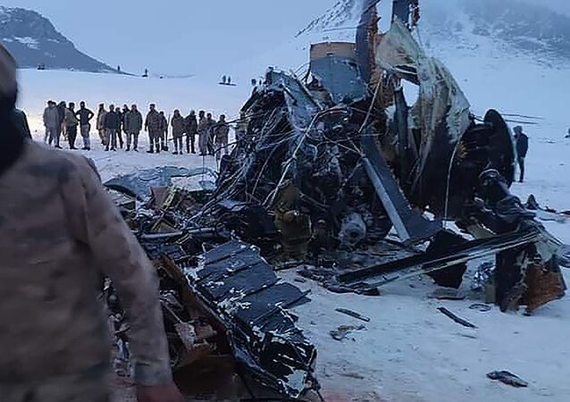 Soldiers and rescue workers stand around the wreckage after an army helicopter crashed in Bitlis, eastern Turkey, Thursday March 4, 2021