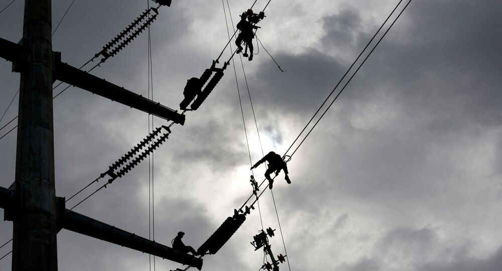 Technicians work on an electricity transmission tower on the outskirts of Yangon on July 8, 2020