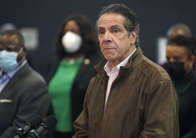 In this 22 February 2021 photo, New York Gov. Andrew Cuomo, right, pauses to listen to a reporter's question during a news conference at a COVID-19 vaccination site in the Brooklyn borough of New York