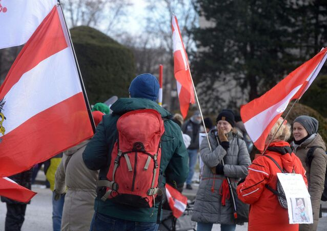 Demonstrators wave Austrian flags as they protest against the restrictions and measures taken by the Austrian government to fight the novel coronavirus, on 13 February 2021 in Vienna, amid the novel coronavirus / COVID-19 pandemic.