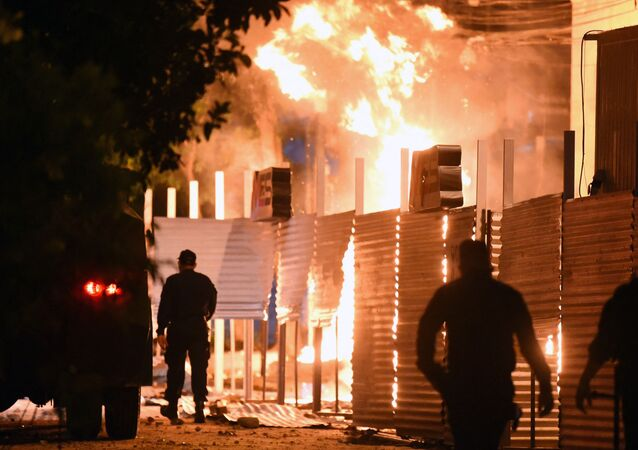 Policemen are seen near a fire set on by demonstrators at the Commerce Ministry headquarters during a protest against corruption and lacks in the health system, demanding the resignation of Paraguayan President Mario Abdo Benitez, in Asuncion, on March 5, 2021.